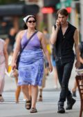Barbie Ferreira wears a purple top and blue floral print skirt while out for a walk with a friend in New York City