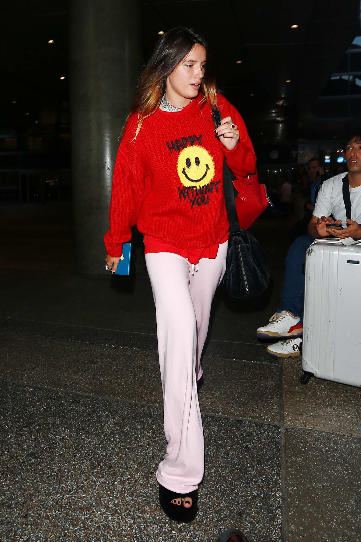 Bella Thorne seen wearing a red sweater as she arrives make-up free at LAX in Los Angeles