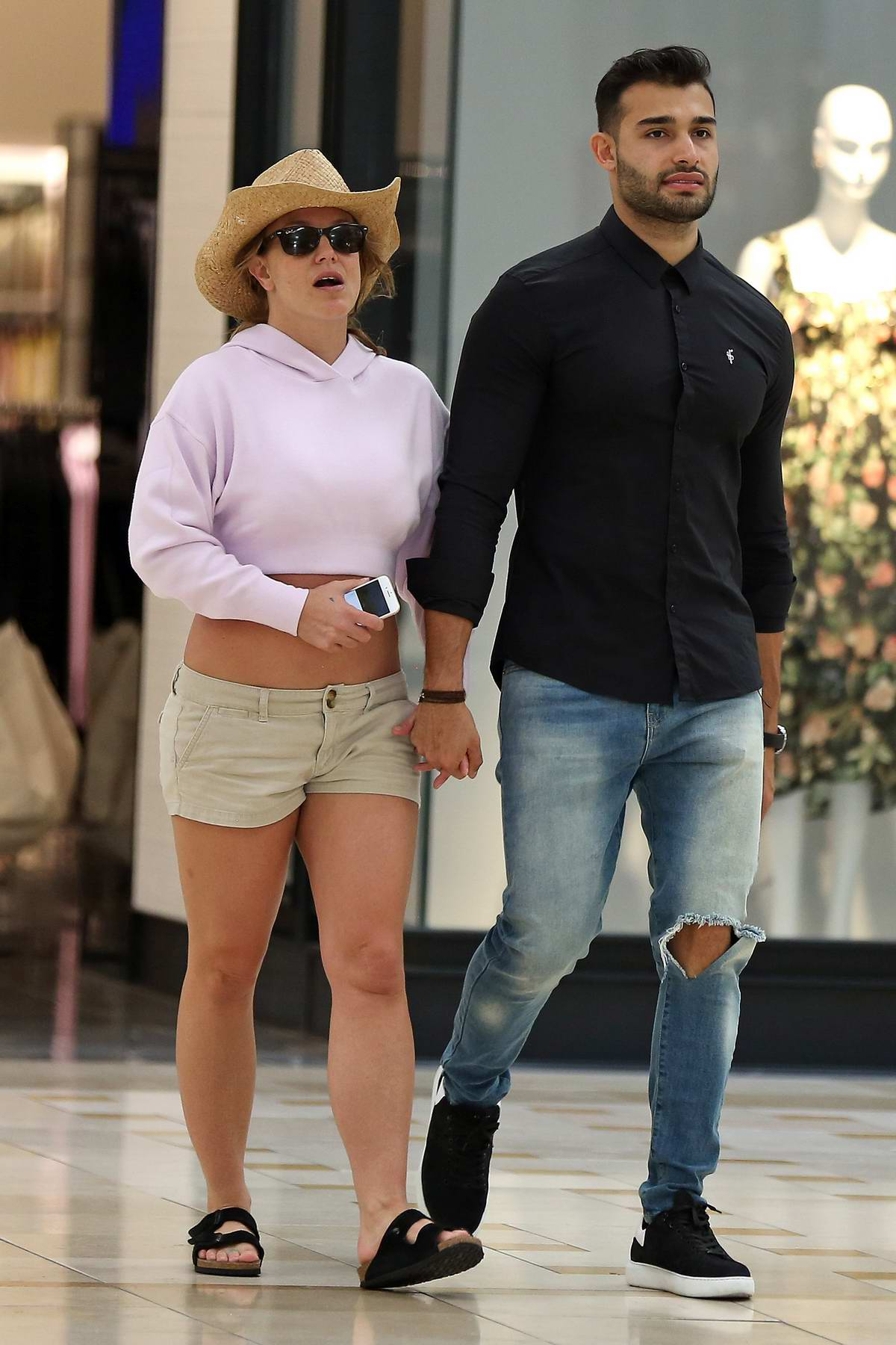 Britney Spears wears a pink crop and beige shorts while out with boyfriend Sam Asghari in Los Angeles