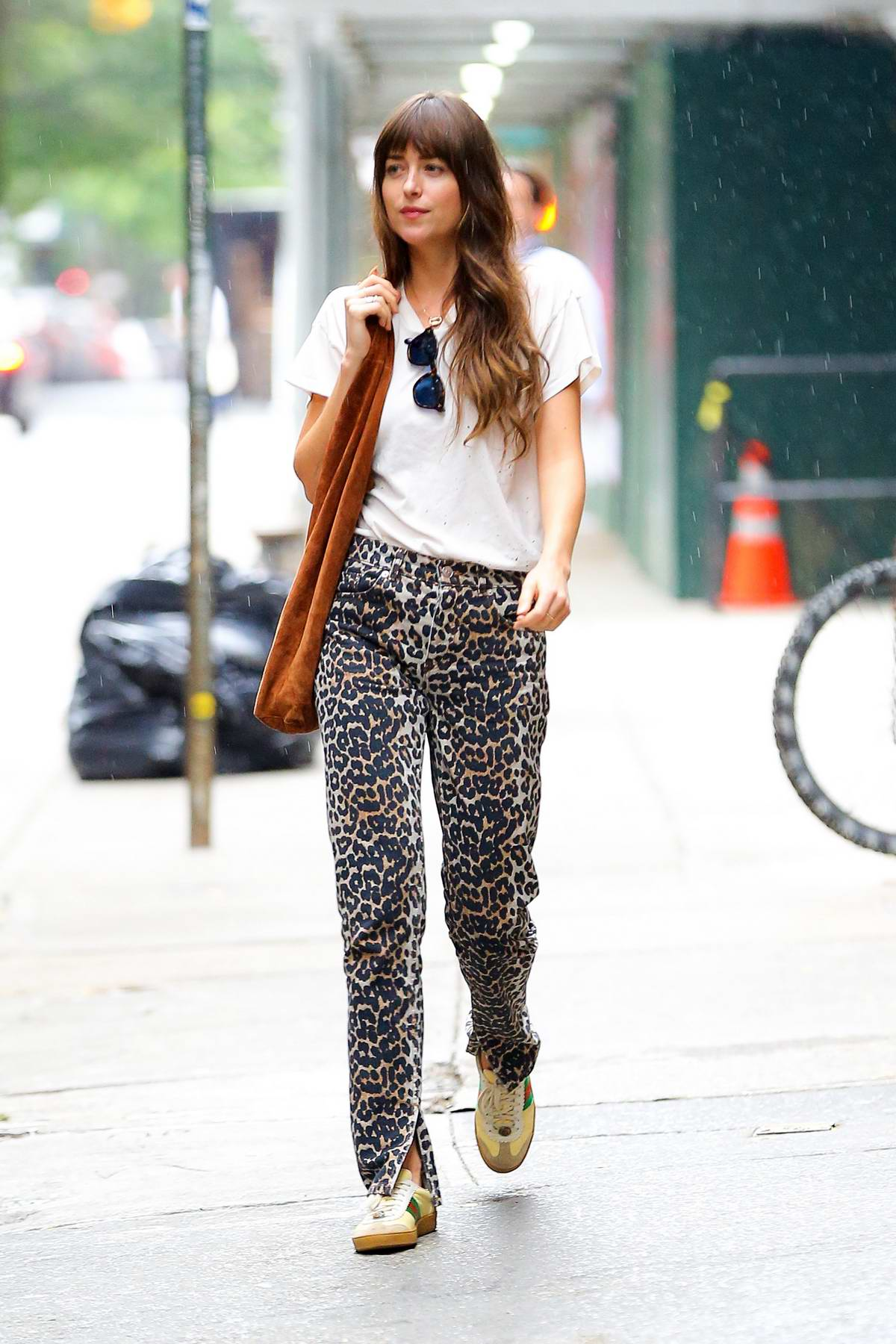 Dakota Johnson steps out on a rainy day donning a white tee and animal print pants in New York City