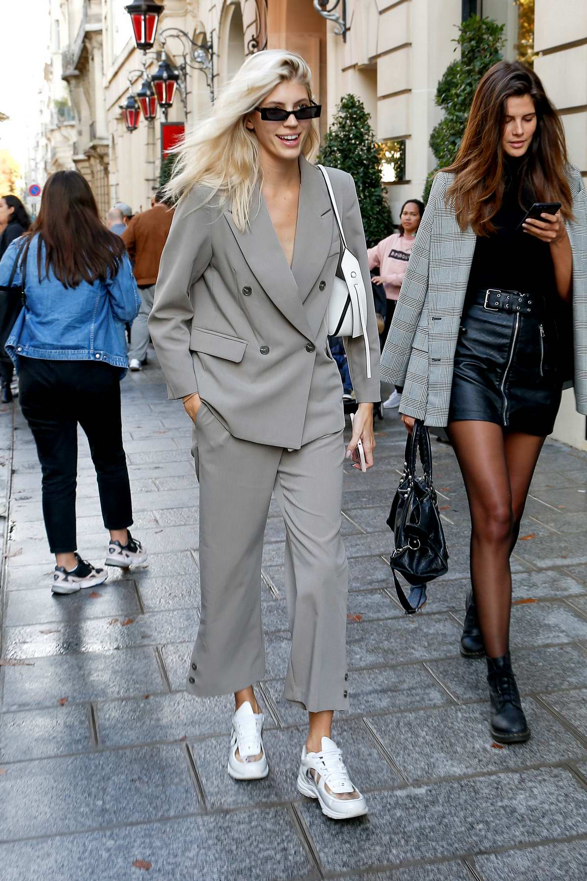Devon Windsor wears a grey suit with white Chanel sneakers as she leaves her hotel during PFW in Paris, France