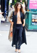emily ratajkowski rocks a full-length trench coat over a white bikini top with black trousers while out in new york City