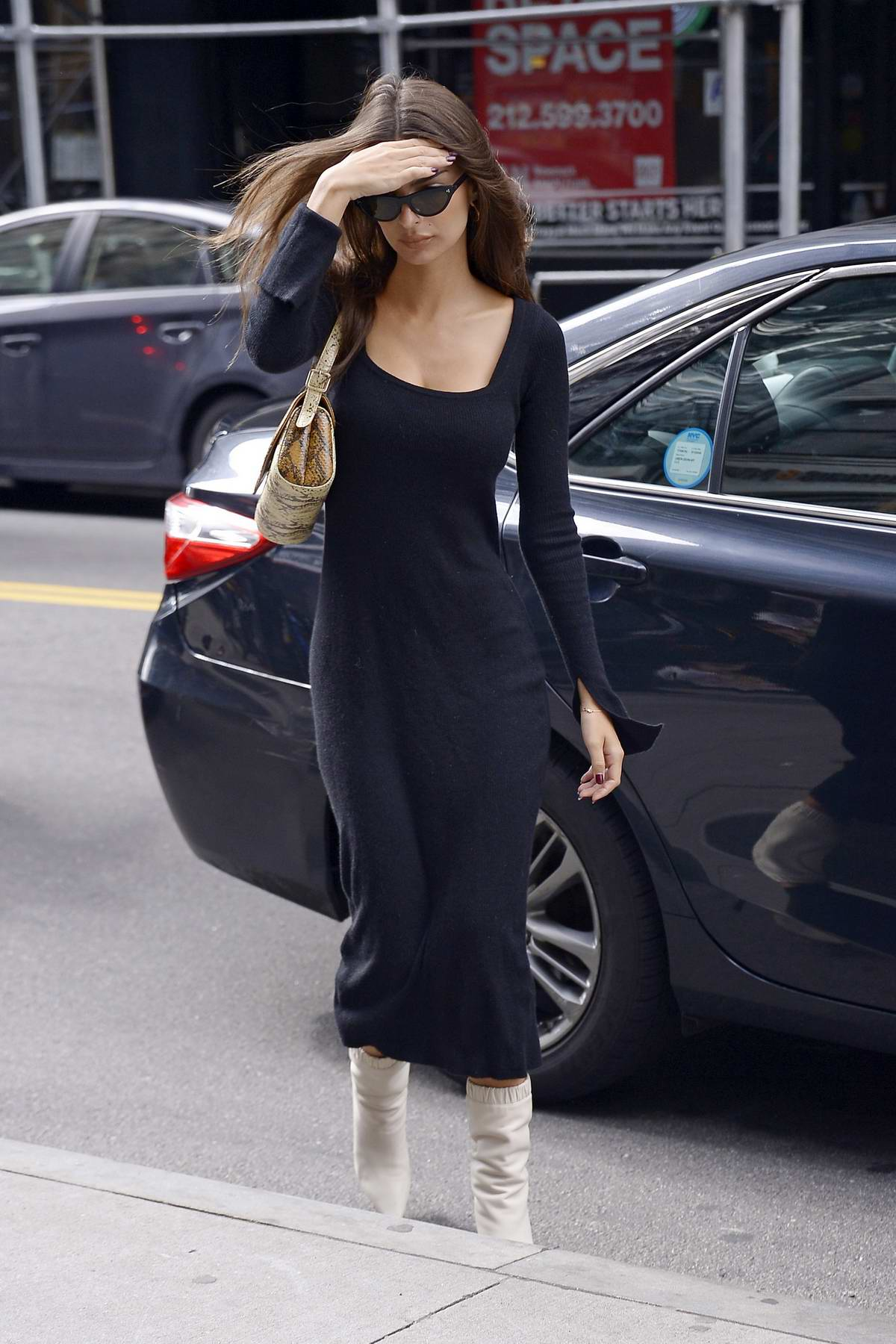 Emily Ratajkowski seen wearing a black long dress and white boots as she arrives at an office building in New York City