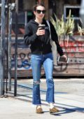 Emma Roberts wears a black hoodie and ripped jeans while out for a coffee in Los Angeles