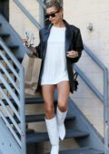 Hailey Baldwin rocks black leather jacket with a white mini dress and knee high boots while out shopping in Los Angeles