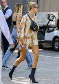 Hailey Baldwin shows off he slender legs in a tie-dye dress during a lunch outing with a friend in Bel Air, California