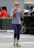 Isla Fisher wears grey 'Good Vibe' tee and purple leggings during a coffee run in Los Angeles