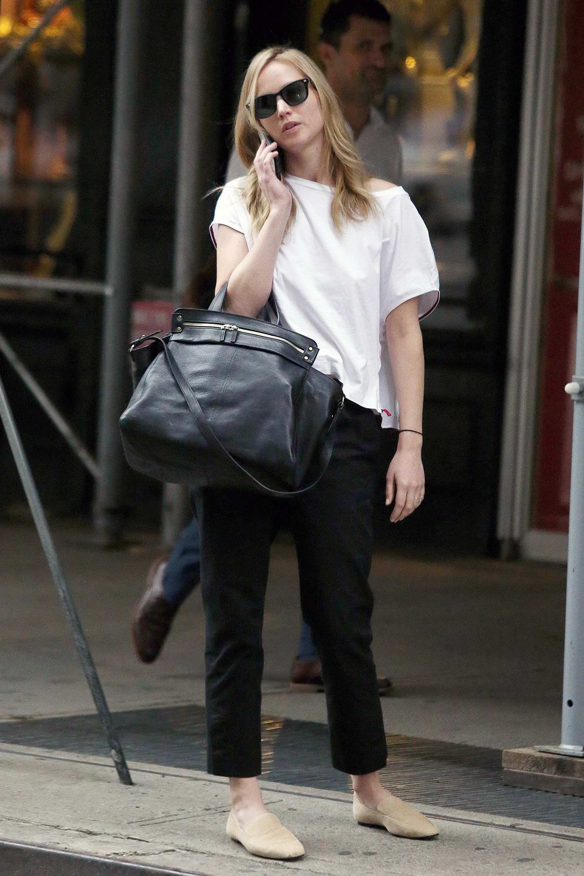 Jennifer Lawrence wears a white t-shirt and black trousers during a visit to a hair salon in New York City