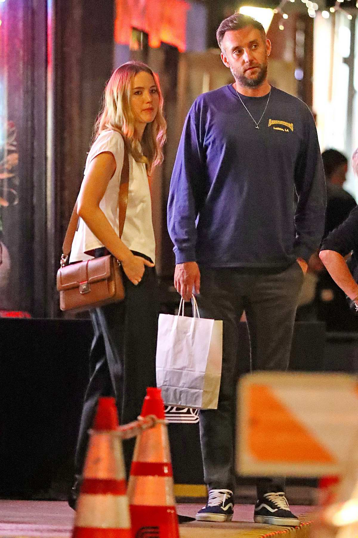 Jennifer Lawrence wears a white top and black trousers during a date night with Cooke Maroney in New York City