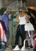 Jennifer Lopez braves the rain with a clear umbrella as she leaves her hotel in Miami Beach, Florida