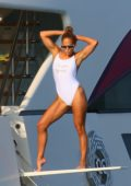 Jennifer Lopez poses in a white swimsuit during a photoshoot on her yacht in Saint-Tropez, France