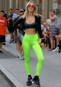 Joy Corrigan looks striking in neon green leggings and a sports bra while posing for photos in SoHo, New York City