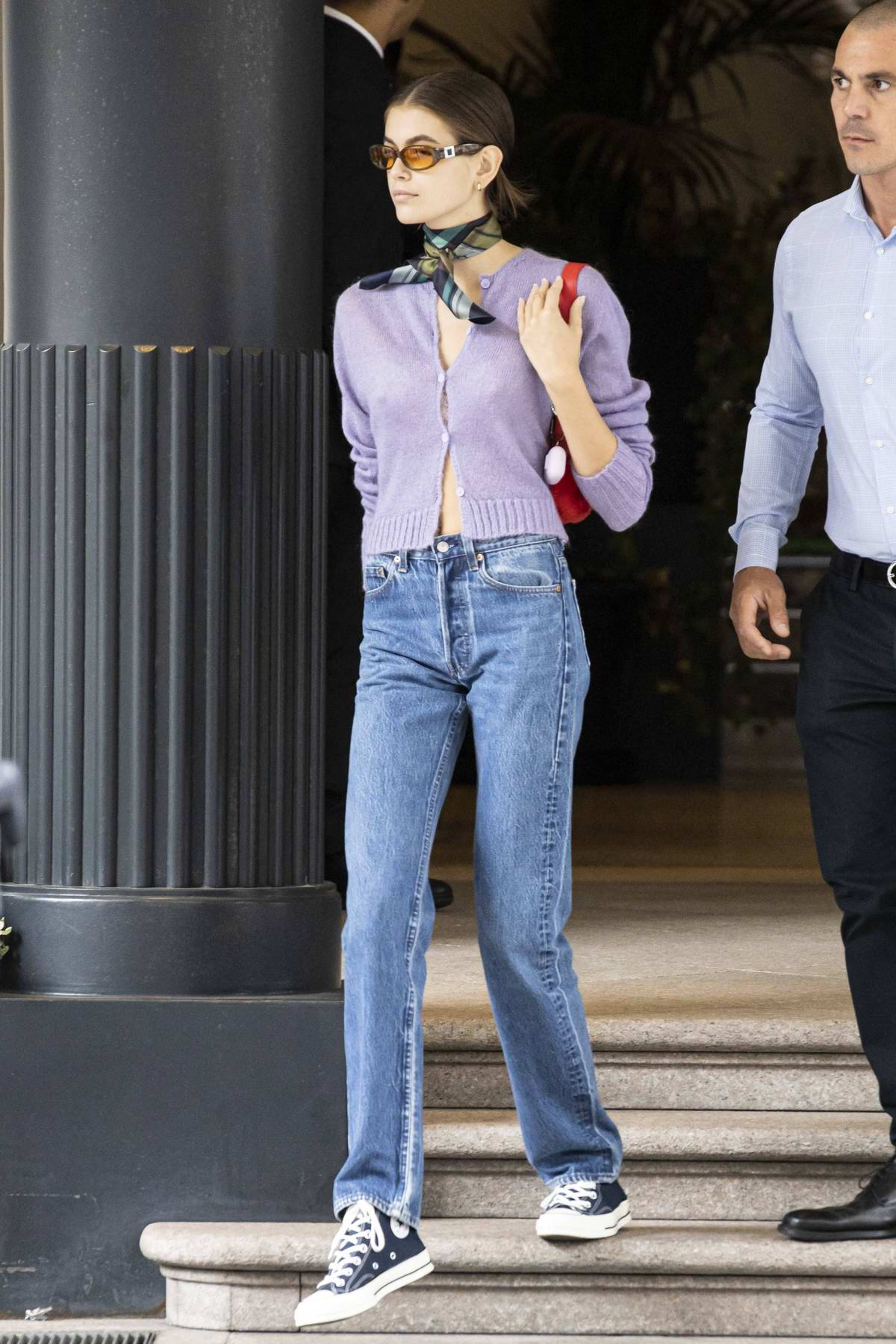 Kaia Gerber steps out in a cropped purple cardigan and jeans during Milan Fashion Week in Milan, Italy