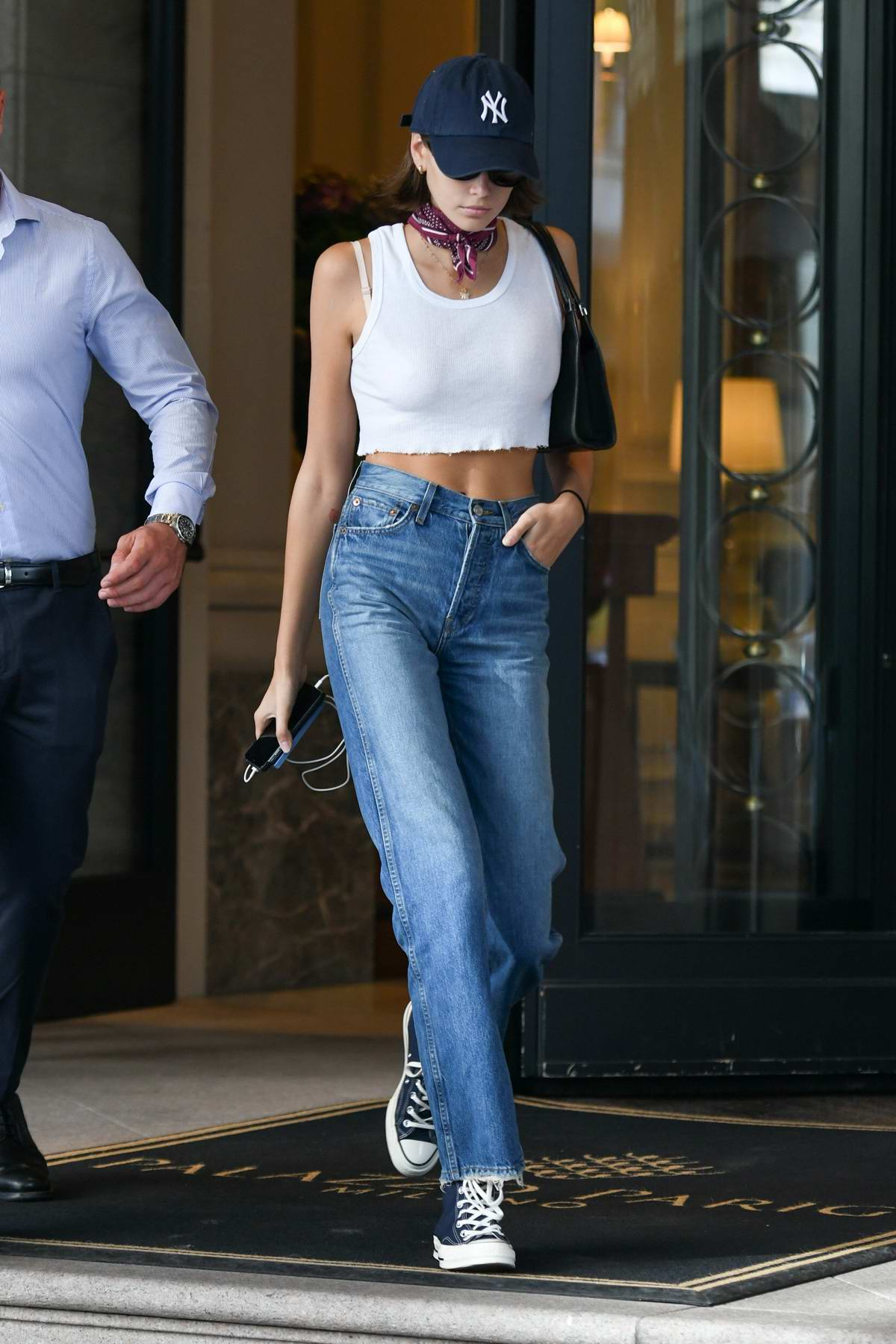 Kaia Gerber wears a cropped white tank top with jeans and Converse while stepping out during Milan Fashion Week in Milan, Italy
