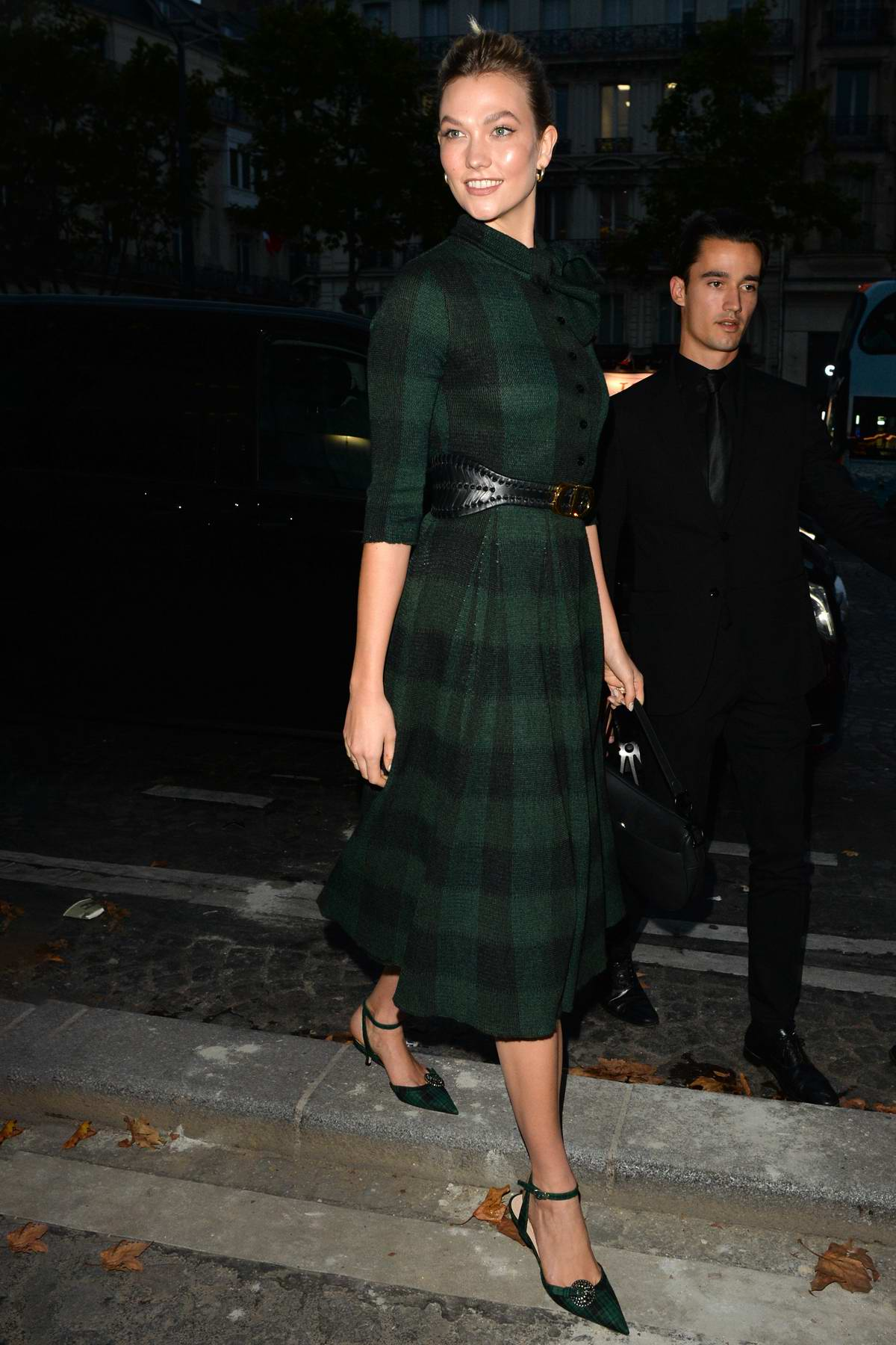 Karlie Kloss is all smiles while out wearing a green and black plaid dress in Paris, France
