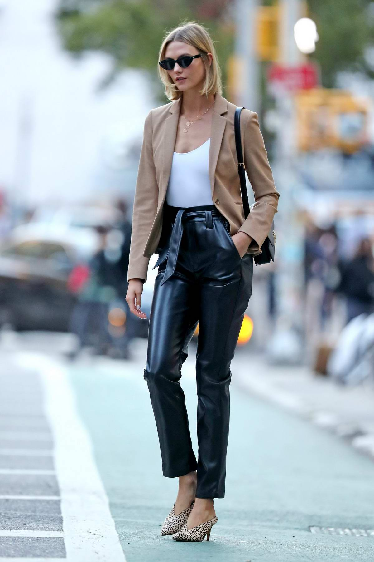 Karlie Kloss looks fashionable in a beige blazer and black leather pants as she steps out in New York City