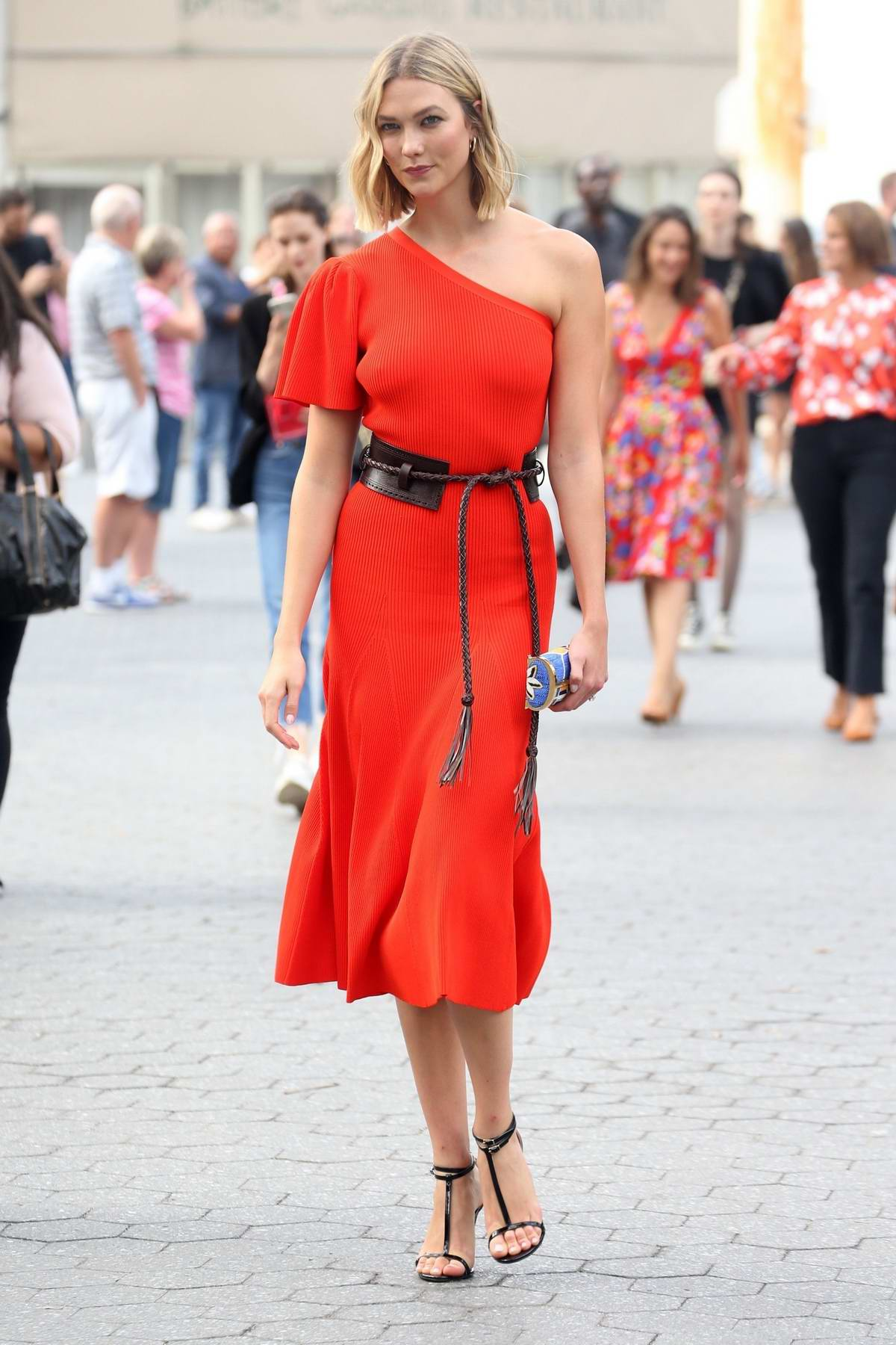 Karlie Kloss stuns in an orange dress while attending Carolina Herrera Show during New York Fashion Week in New York City