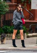 Katie Holmes wears a grey sweater with black mini skirt and studded boots while out on a stroll in New York City