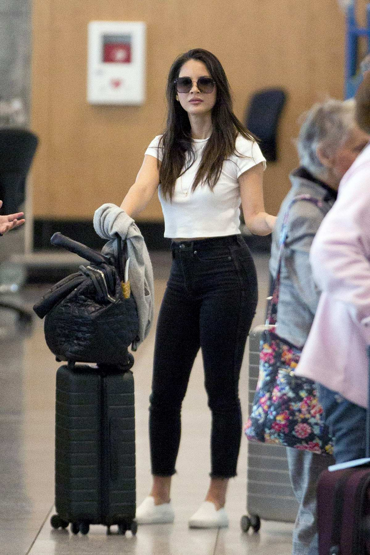 Olivia Munn steps out for a stroll with her trainer before heading over to the airport in Montreal, Canada