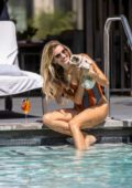 Rachel McCord wears an orange swimsuit as she cools down with her dog at La Peer Hotel in Hollywood, California