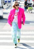 Rita Ora rocks a fuchsia blazer and colorful tie-dye sweatpants as she heads to Heathrow airport in London, UK