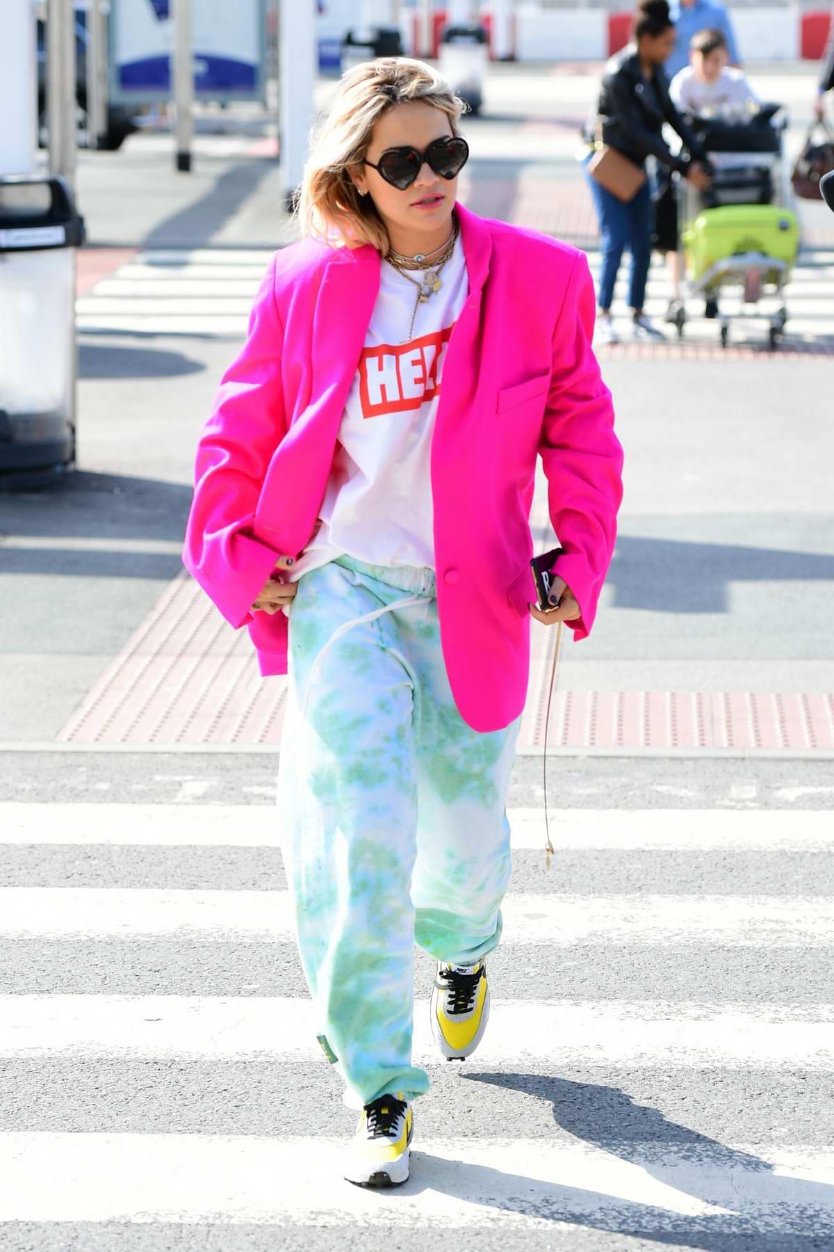 Rita Ora rocks a fuchsia blazer and colorful tie-dye sweatpants as she heads to Heathrow airport in London, UK