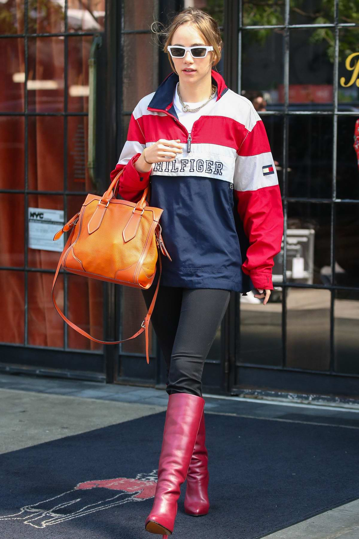 Suki Waterhouse rocks Hilfiger pullover with a black pants and knee high burgundy boots as she steps out in New York City