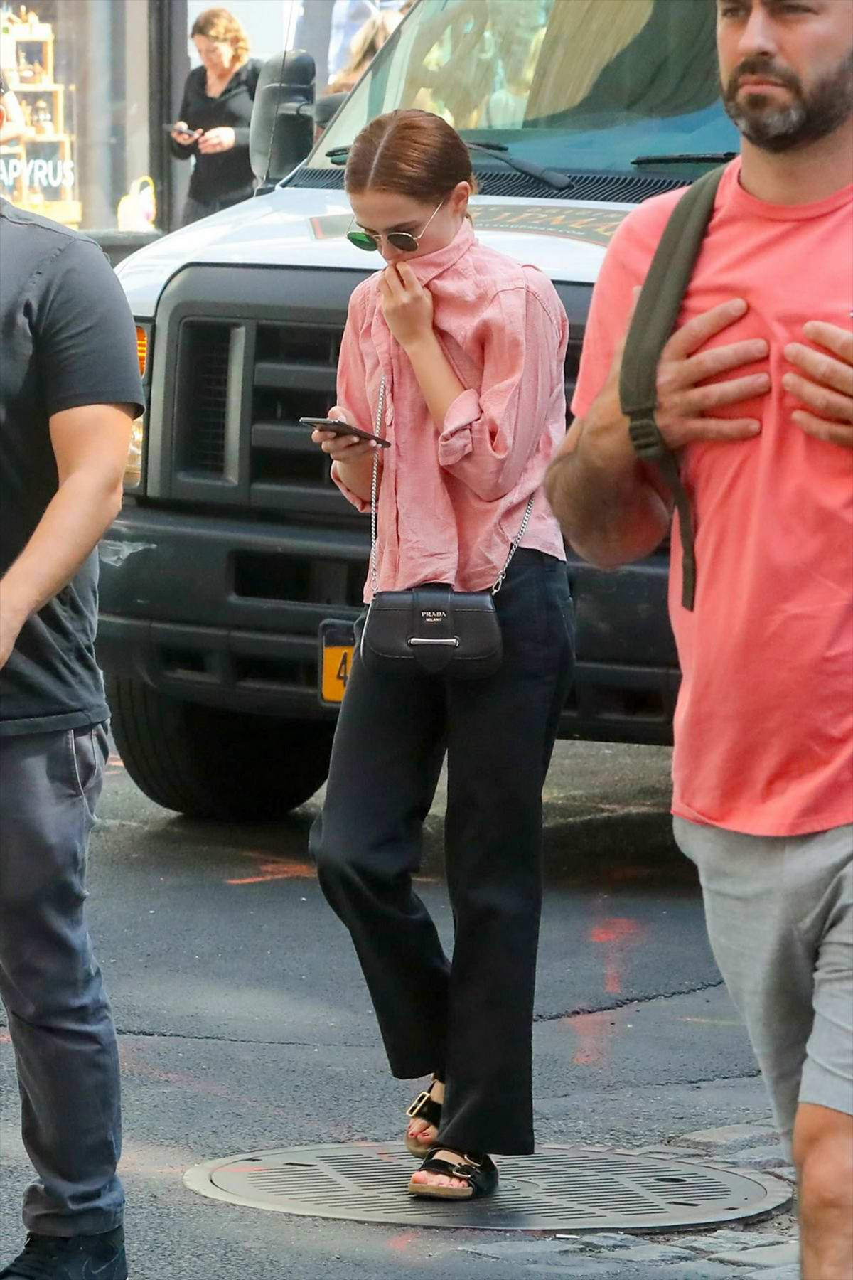 Zoey Deutch steps out in a pink shirt and black trousers with Prada purse in New York City
