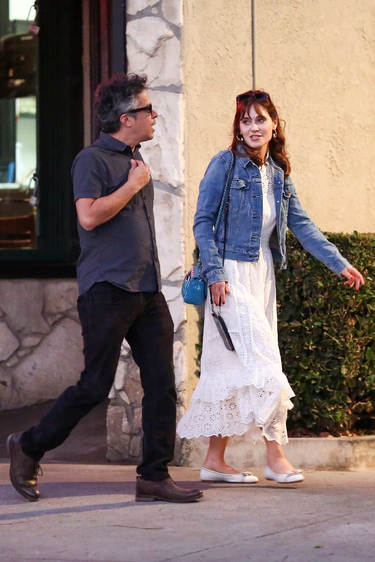 Zooey Deschanel looks lovely in a denim jacket with white dress while out with a friend in Los Angeles