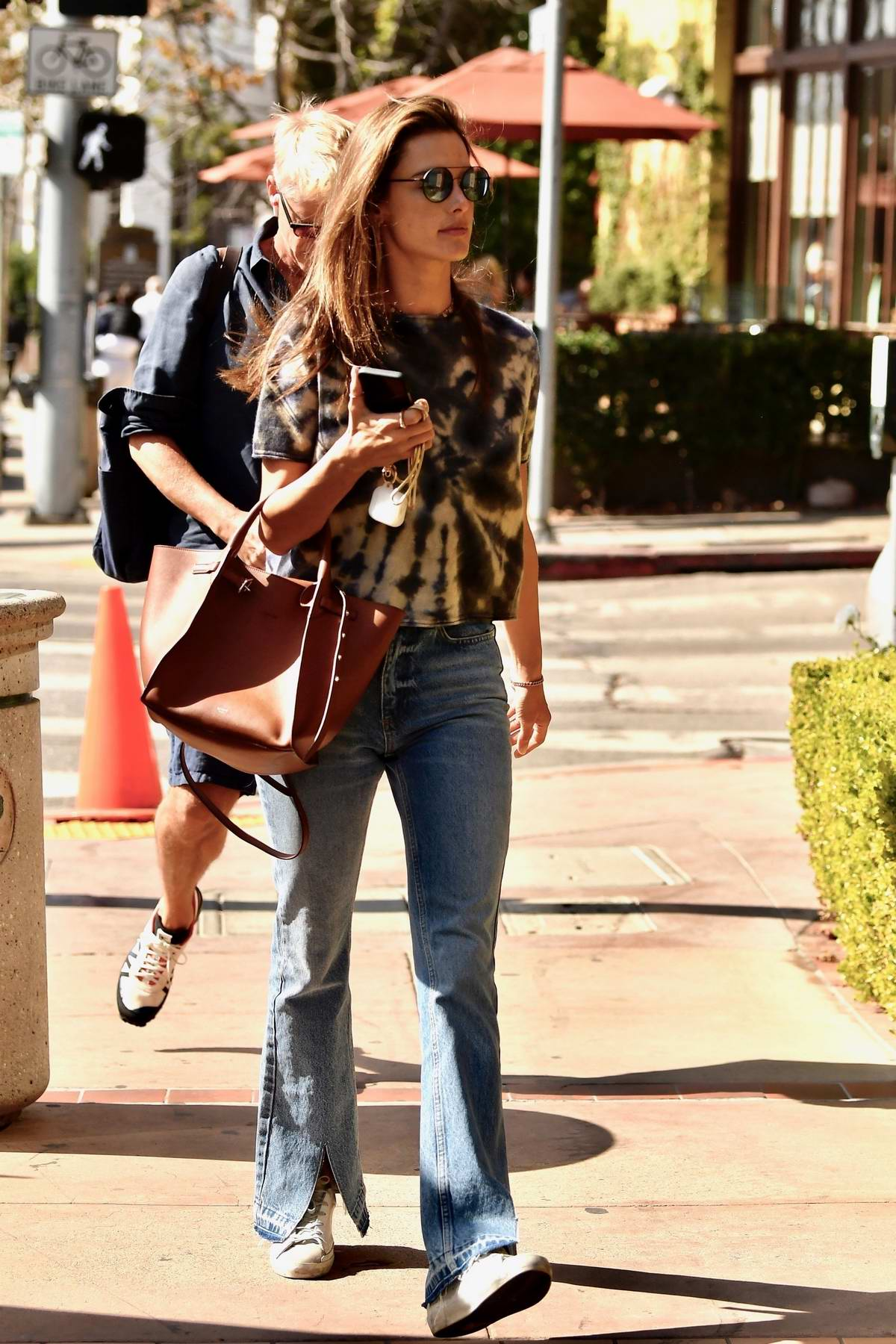 Alessandra Ambrosio rocks a tie-dye top and flared jeans while out for lunch at Toscano in Brentwood, Los Angeles