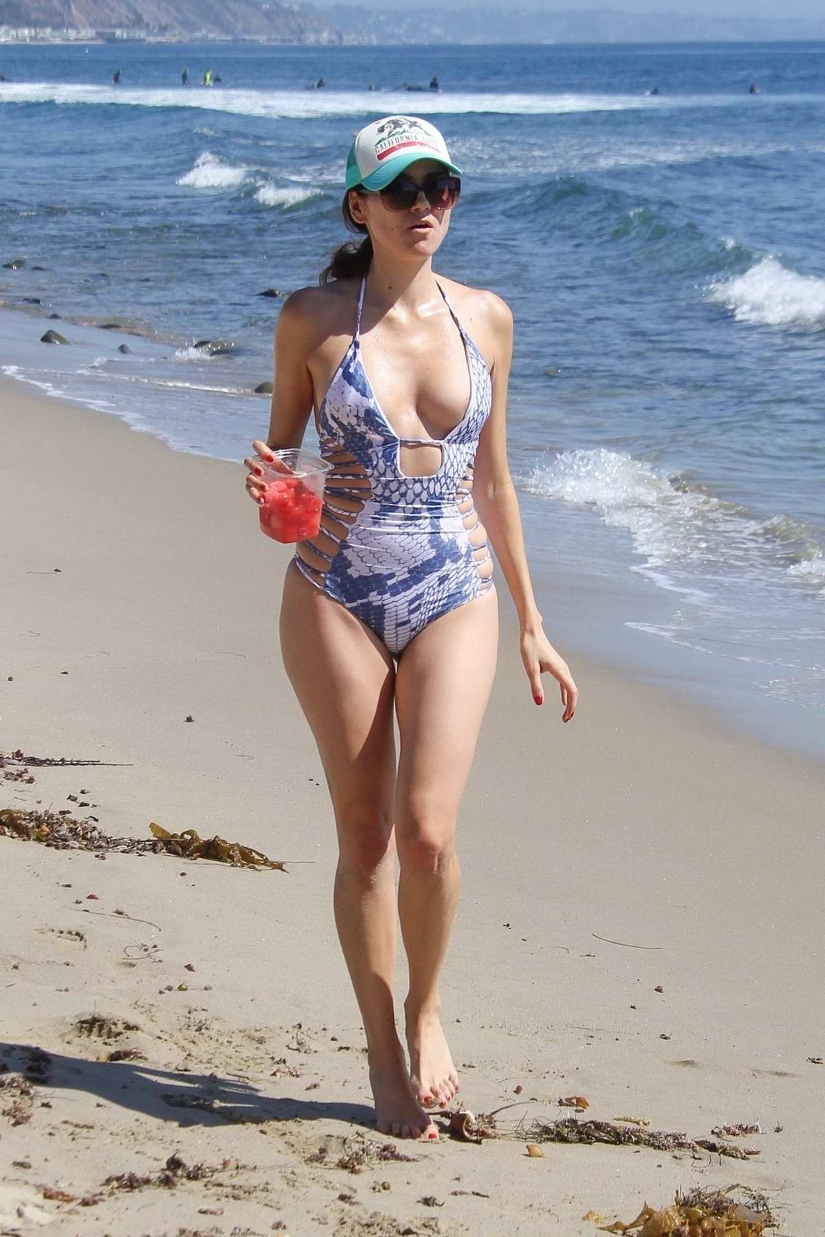 Blanca Blanco wears a blue and white patterned swimsuit while enjoying some watermelon on the beach in Malibu, California