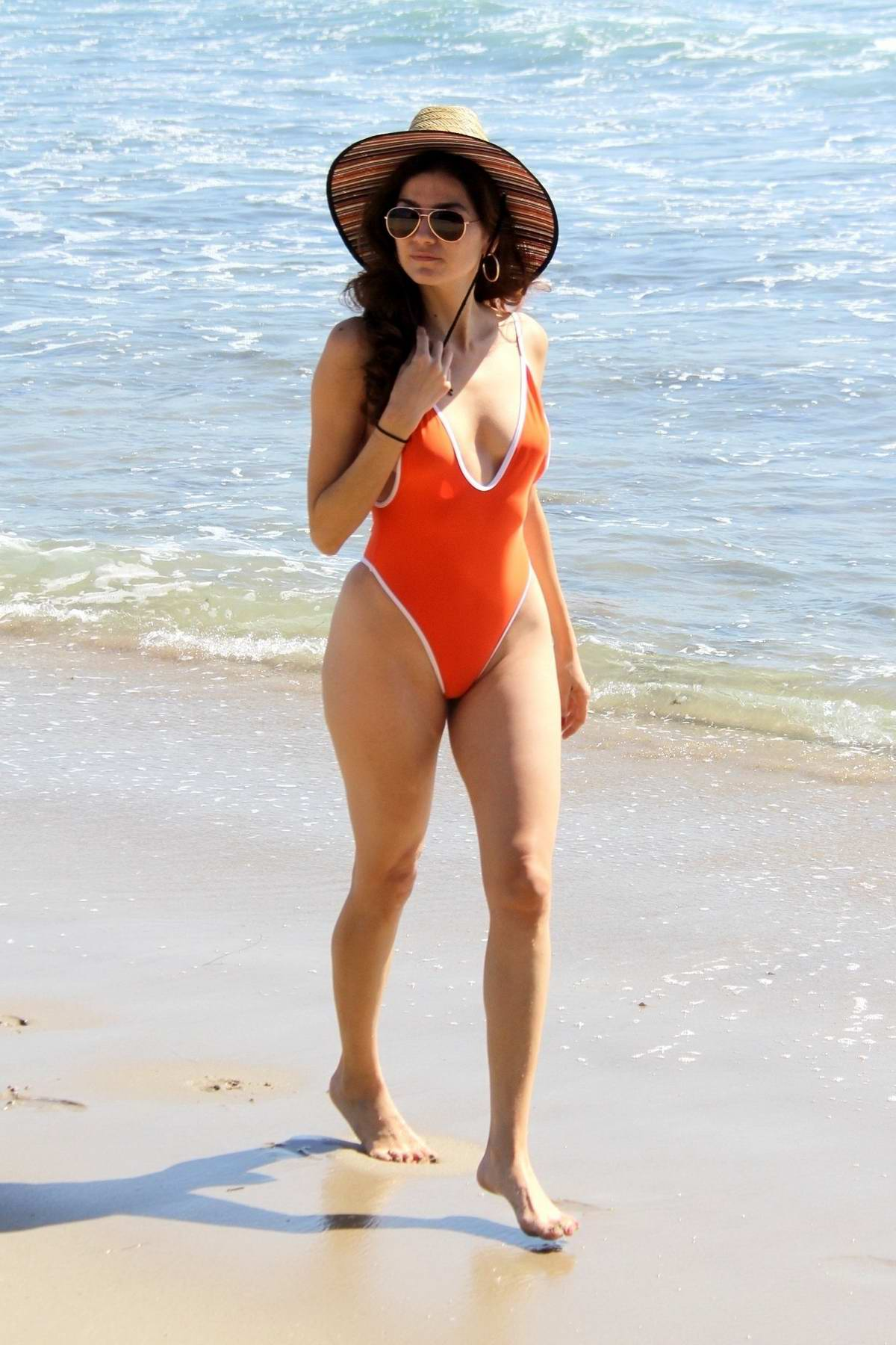Blanca Blanco wears an orange swimsuit while she frolics around the beach in Malibu, California