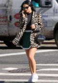 Camila Mendes steps out in an animal print blazer with green mini skirt and Adidas trainers in New York City