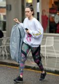 Daisy Ridley wears a white sweatshirt and colorful leggings while picking up some dry cleaning in London, UK