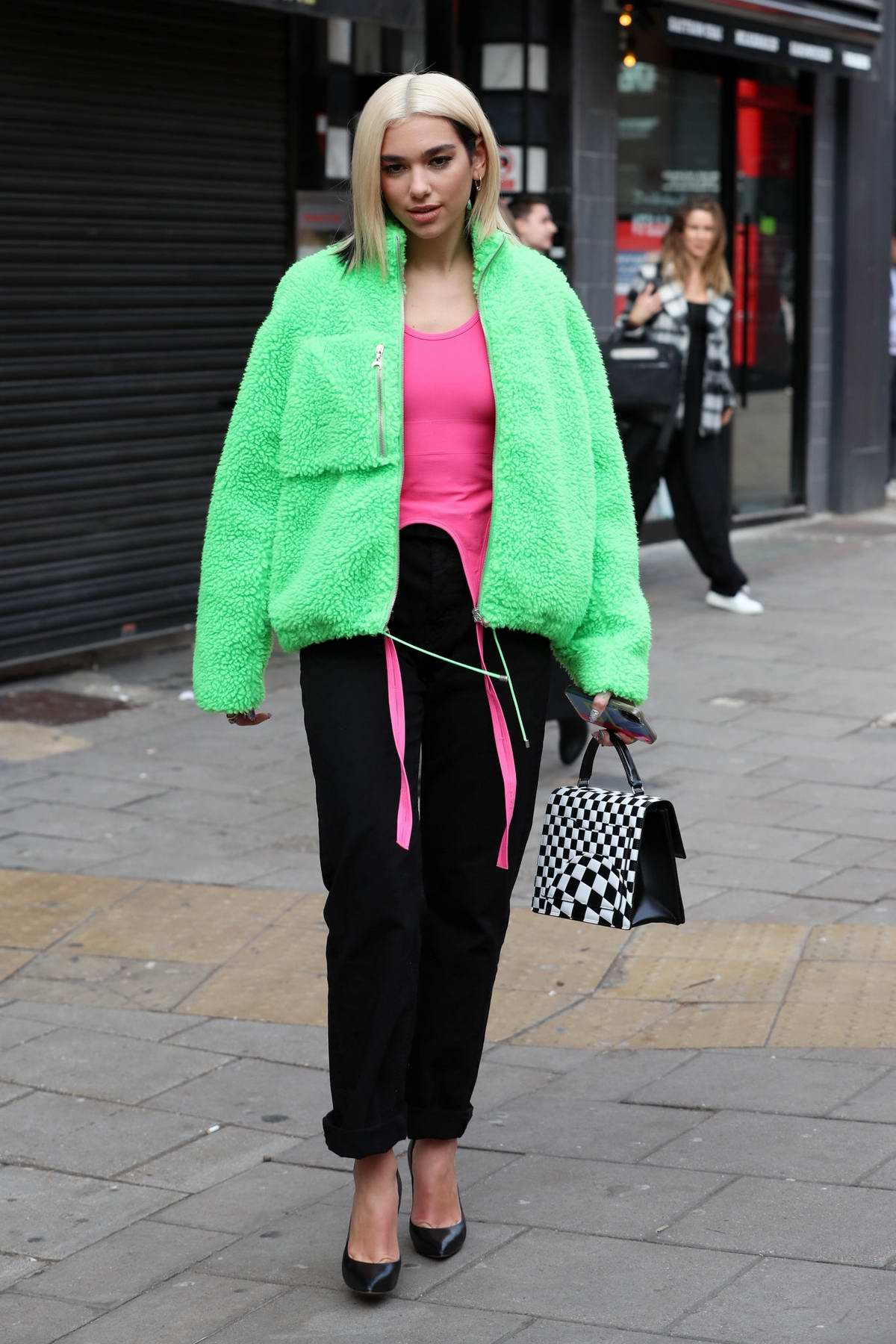 Dua Lipa stands out in a bright green jacket as she leaves Capital ...