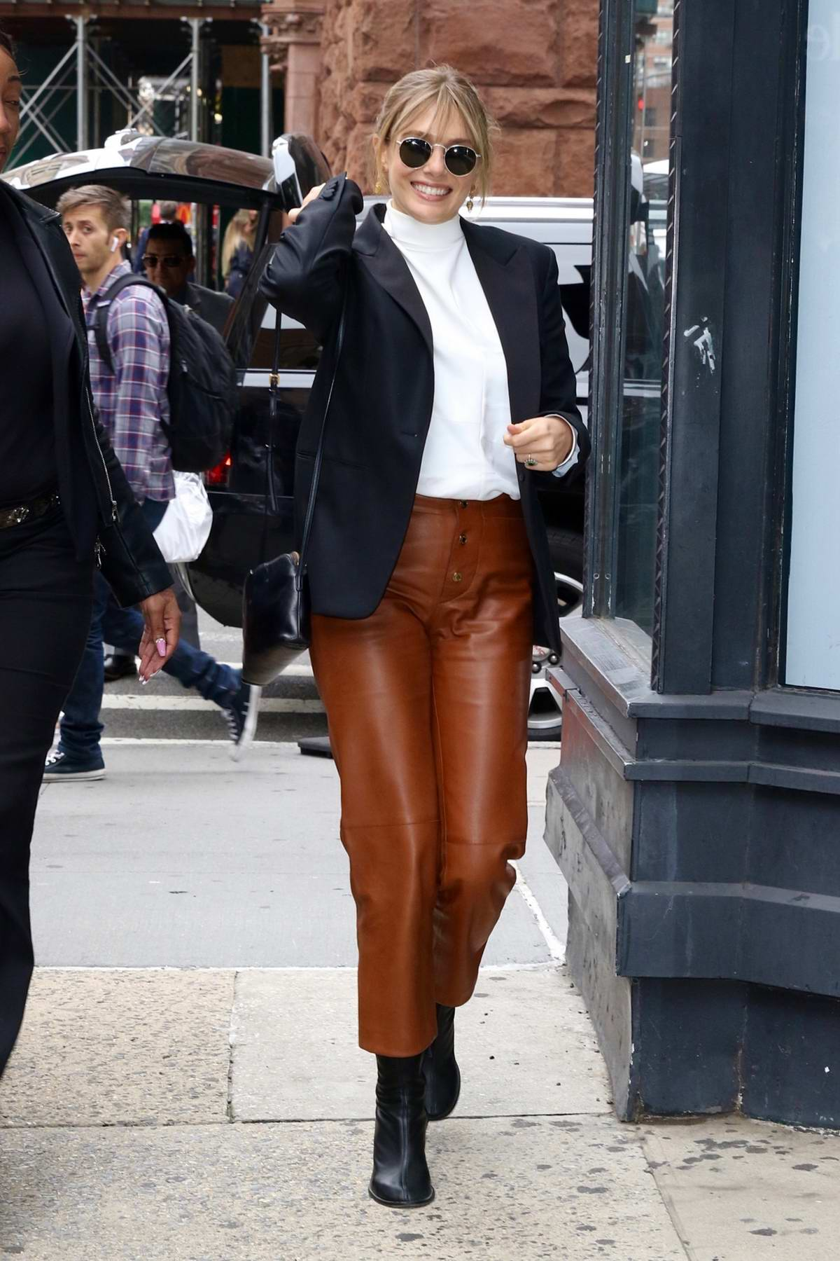 Elizabeth Olsen looks chic in a black blazer and brown leather pants as she arrives at Build Studios in New York City