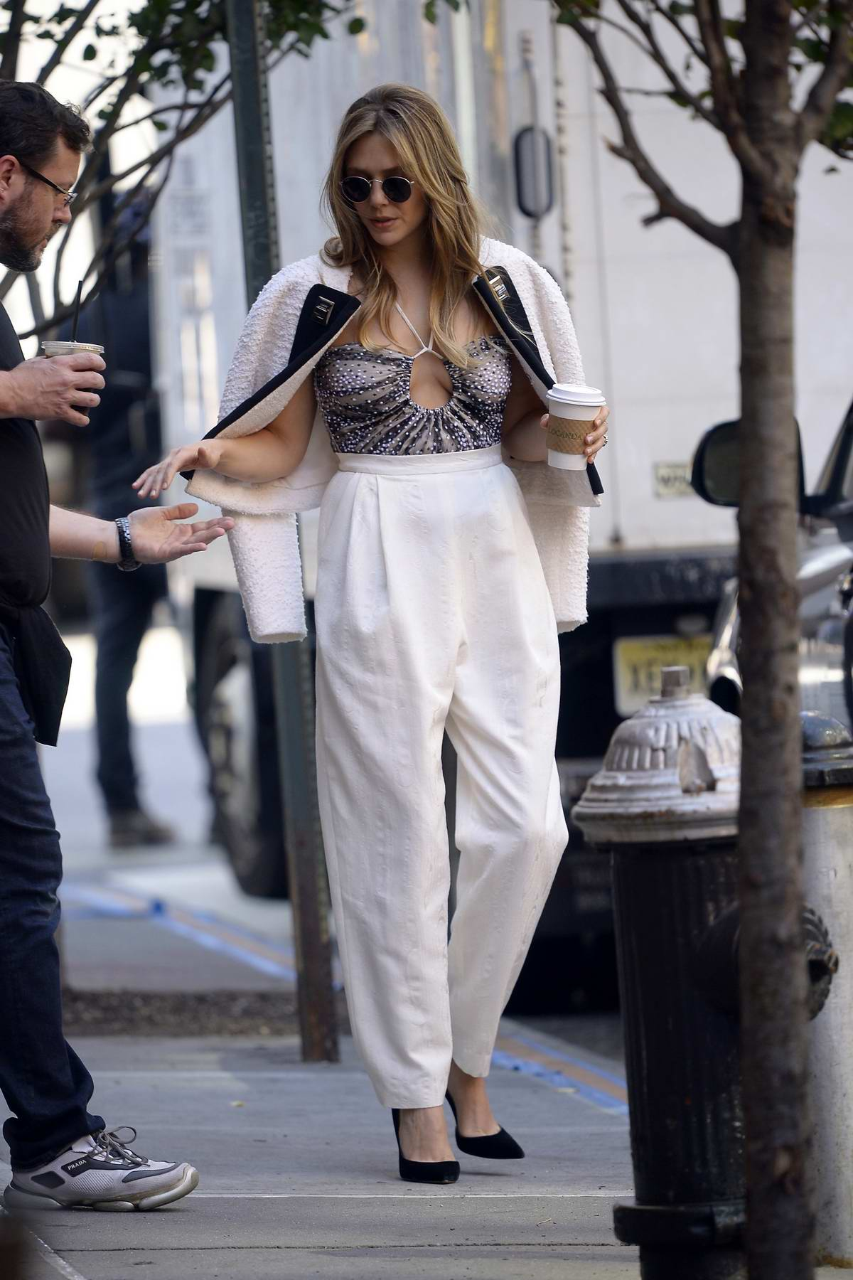 Elizabeth Olsen looks stylish in a spaghetti top and white pants while out in New York City