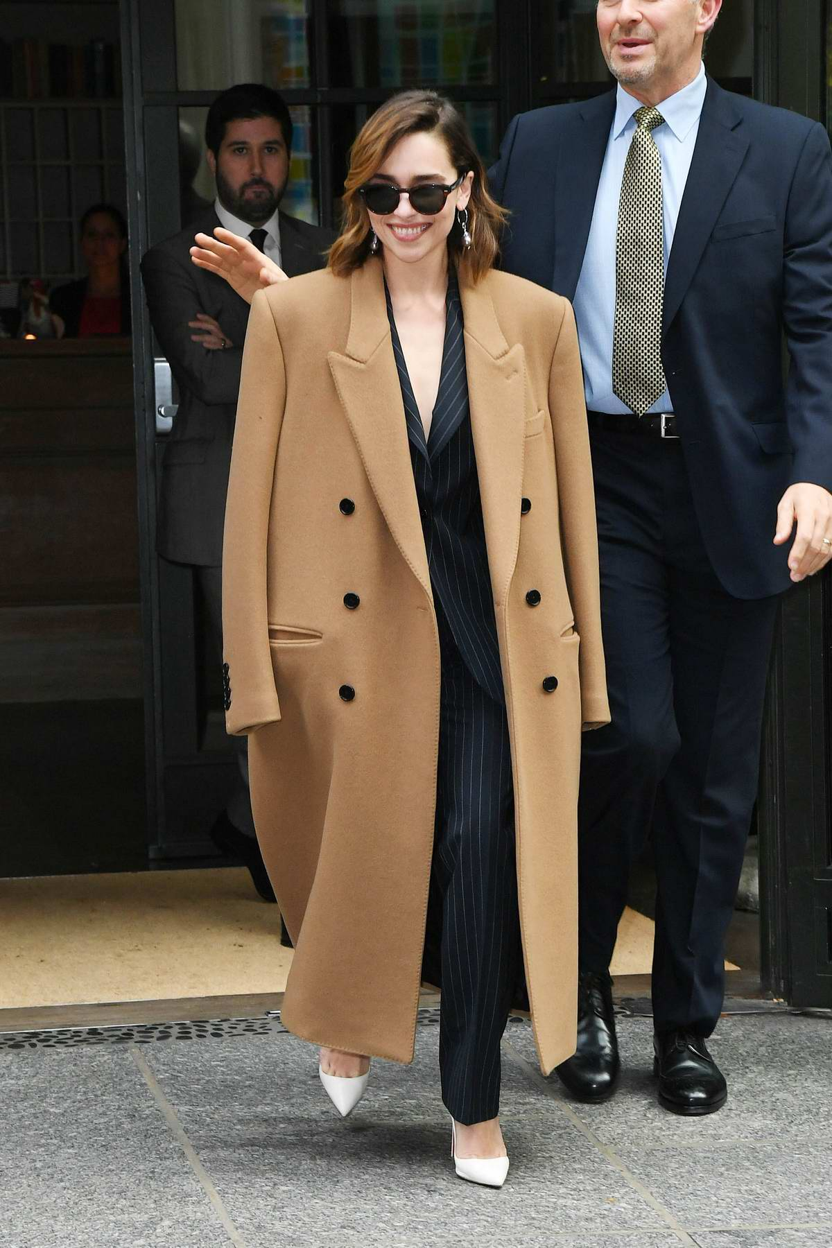 Emilia Clarke seen wearing a pinstriped suit and brown trench coat while out promoting 'Last Christmas' in New York City
