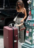 Emily Ratajkowski shows off a messy hair style while out with a large suitcase in New York City
