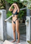Emily Ratajkowski slips into a black bikini while lounging by the pool with her friends in Miami, Florida