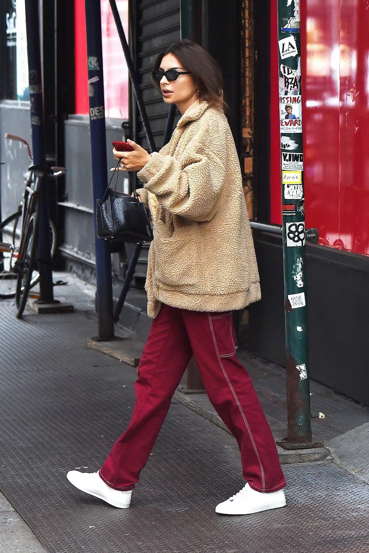 Emily Ratajkowski wears a beige teddy jacket and red trousers while out running errands in New York City