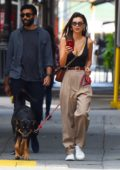 Emily Ratajkowski wears a black low cut tank top and brown trousers as she takes her pup Colombo to the park in New York City