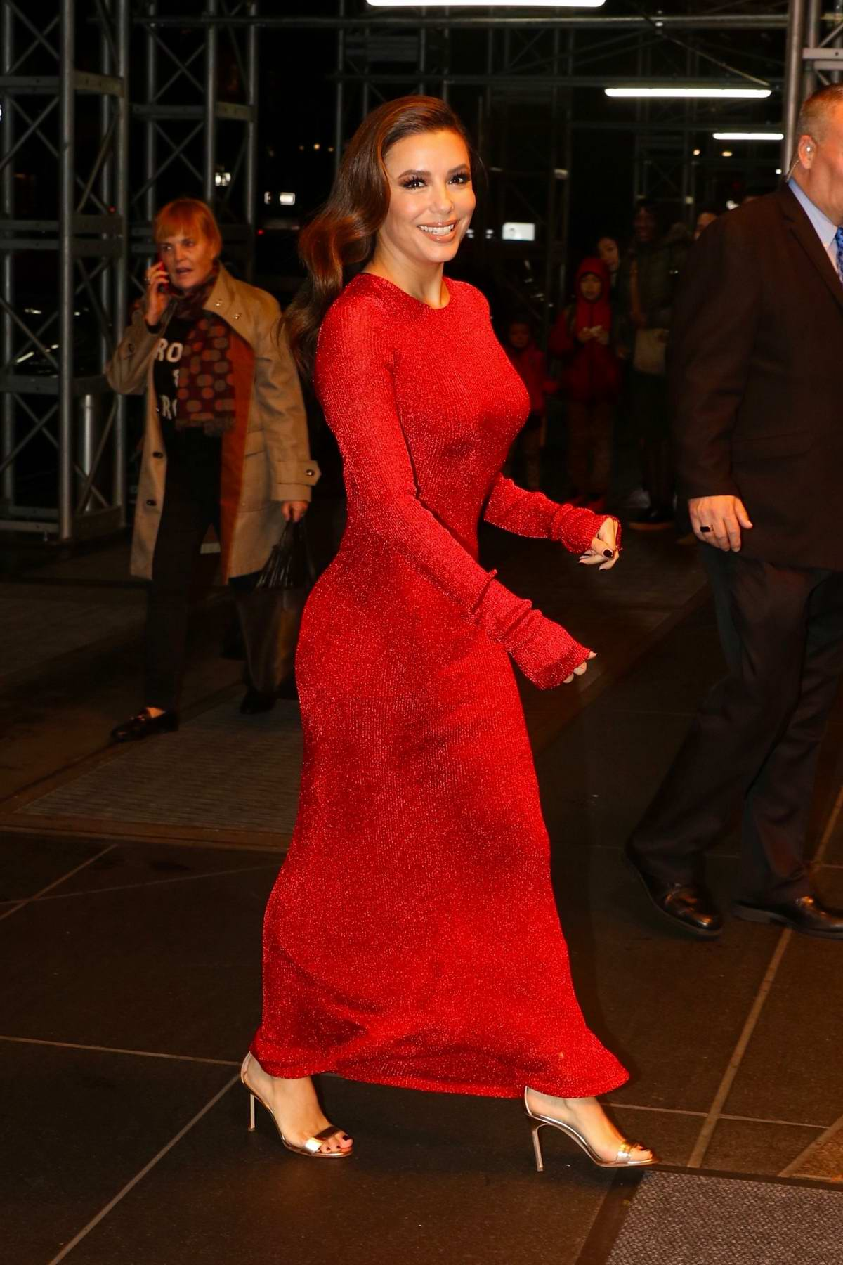 Eva Longoria dazzles in a form-fitting red dress as she arrives at her hotel in New York City