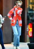 Gigi Hadid is all smiles as she steps out in an orange cardigan in New York City