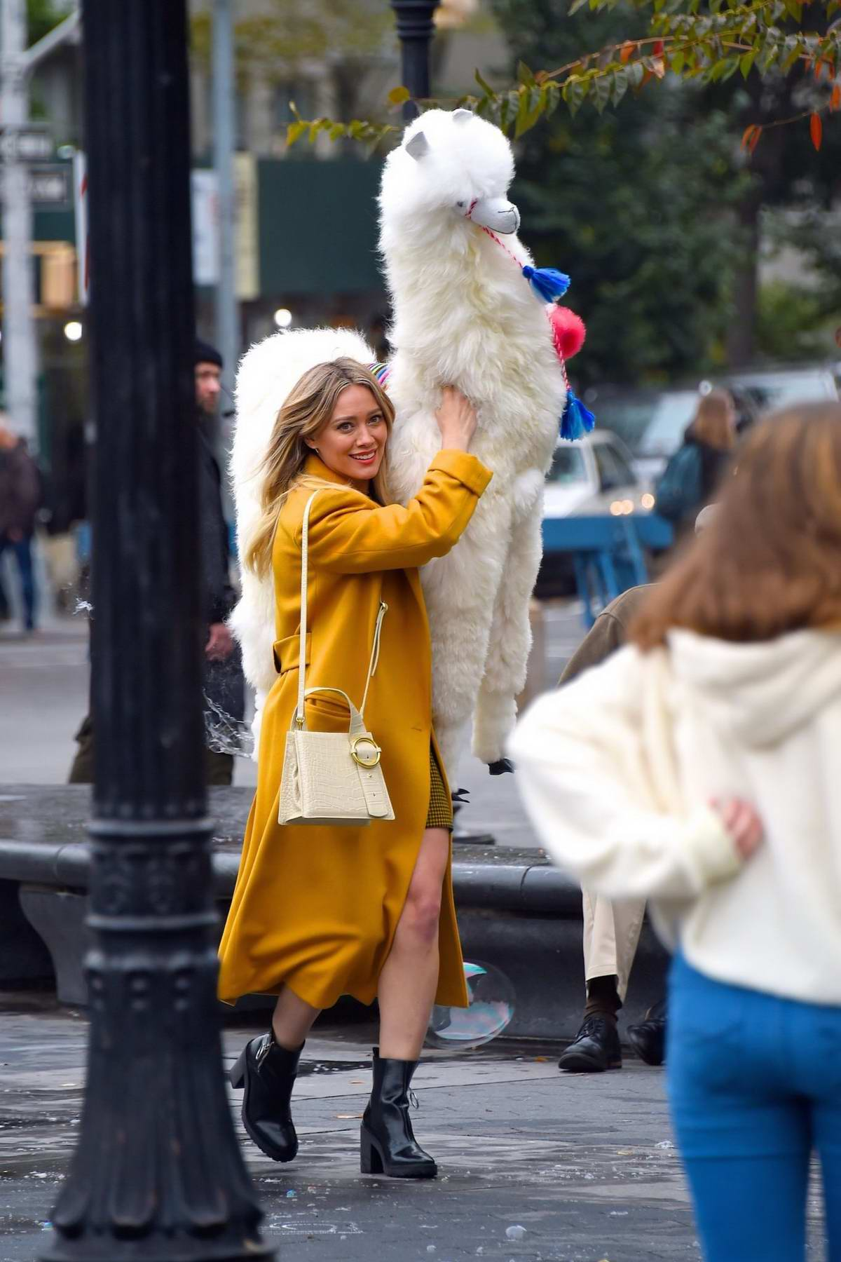 carrying a huge stuffed LlamaHilary Duff seen wearing a mustard yellow trench coat with a matching tartan outfit while carrying a huge stuffed Llama on the set of 'Lizzie McGuire' at Washington Square Park in New York City