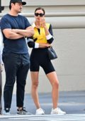 Irina Shayk wears black bike shorts and yellow sport top while stepping out in New York City