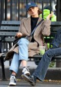 Kaia Gerber shares a few laughs with a friend on a park bench in New York City