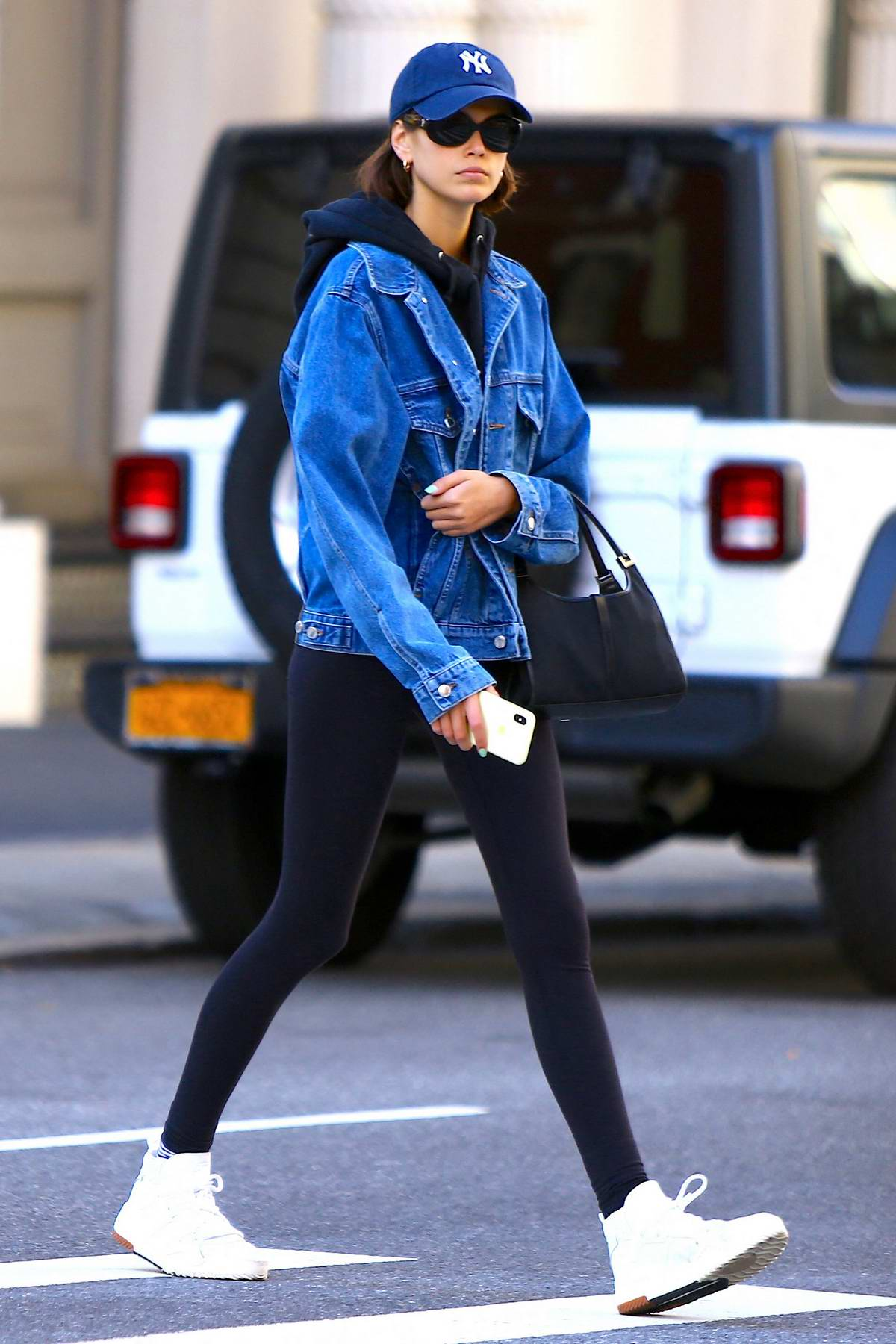 Kaia Gerber sports black leggings with a matching hoodie and denim jacket after a workout session in Soho, New York City