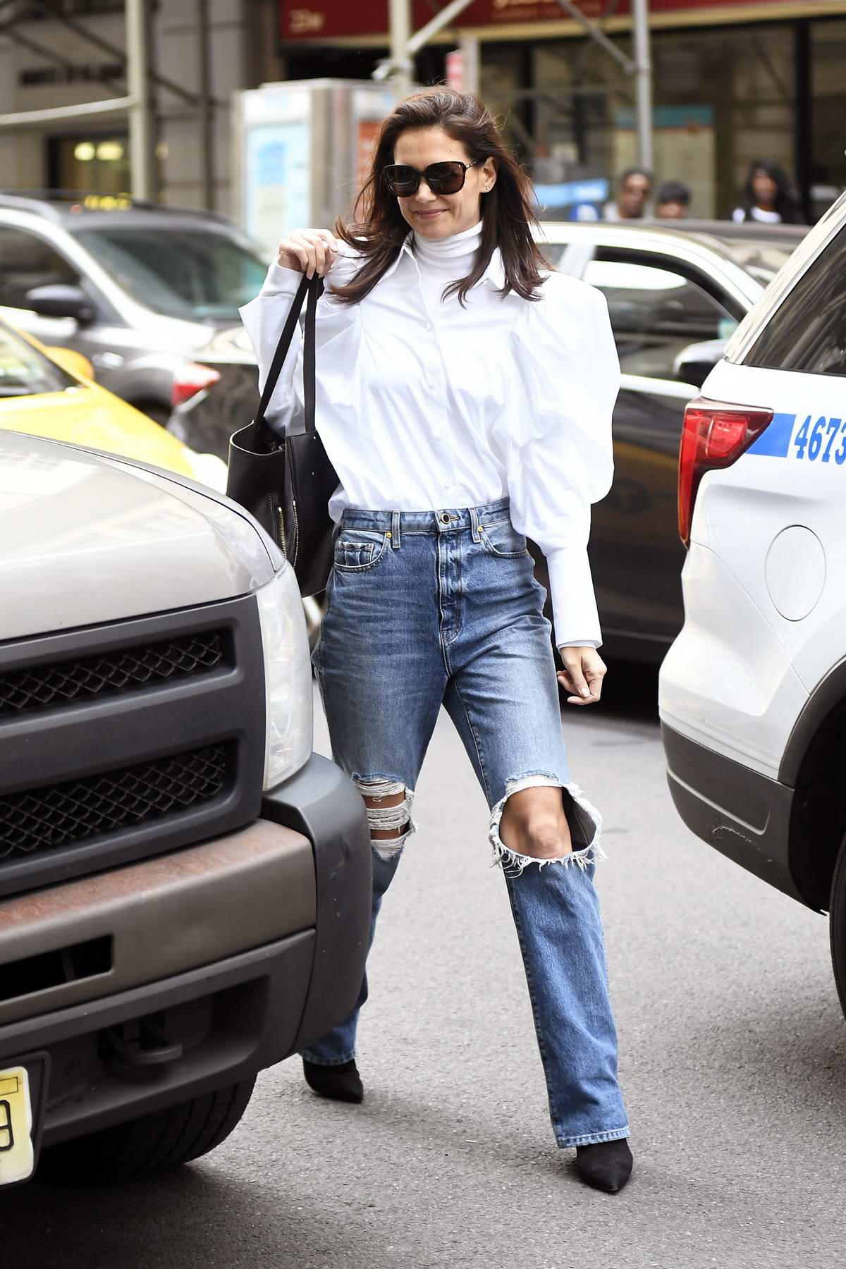 Katie Holmes wears a puffy white shirt and ripped as she steps out for a business meeting in New York City