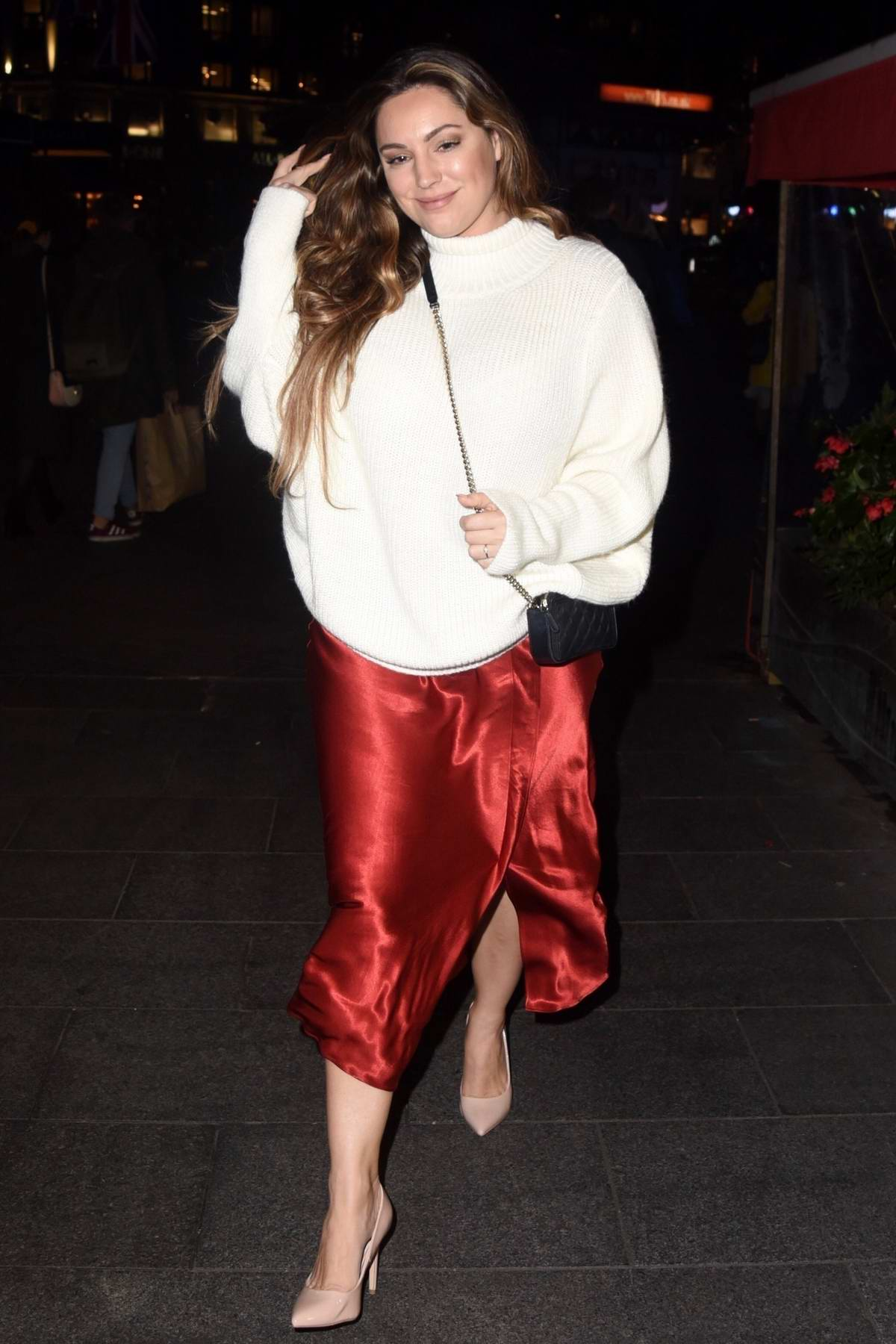 Kelly Brook seen wearing a white jumper and red skirt while leaving Global Radio studios in London, UK